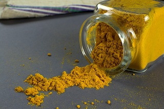 jar of turmeric spice, spilled